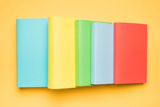 Pila de coloridos libros en blanco sobre fondo amarillo