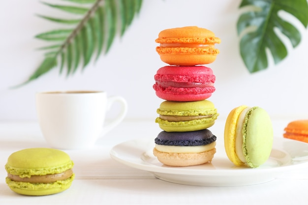 Pila de coloridos macarrones en la mesa con una taza de café