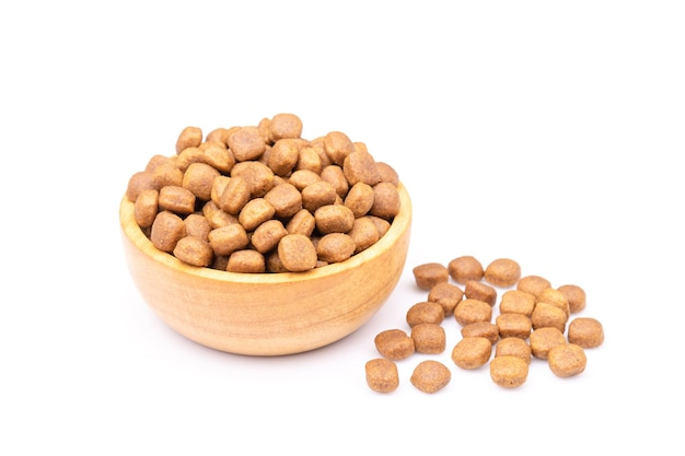 Pila de comida para perros en un tazón de madera aislado sobre superficie blanca