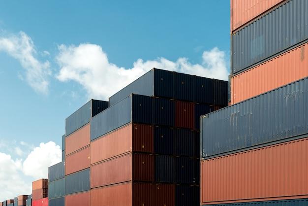 Pila de contenedores de carga en área de importación y exportación en puerto.