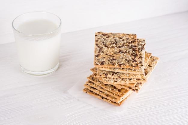 Pila de crujientes tortas de trigo con semillas de sésamo, lino y girasol en una servilleta sobre fondo blanco de madera con vaso de leche. comida vegetariana,