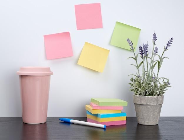 Pila de cuadernos de espiral y pegatinas de colores, junto a una maceta de cerámica con una flor.