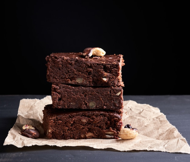 Pila de cuadrados al horno rebanadas de pastel de chocolate brownie con nueces sobre una superficie de madera. comida casera cocinada
