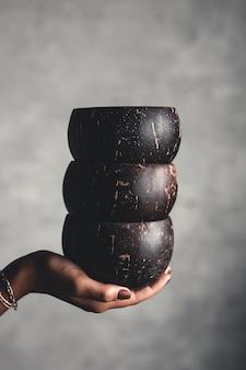 Una pila de cuencos de coco en manos de la mujer. vajilla natural sobre fondo gris.