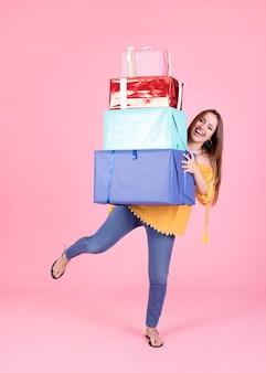 Pila de equilibrio mujer de cajas de regalo sobre fondo rosa