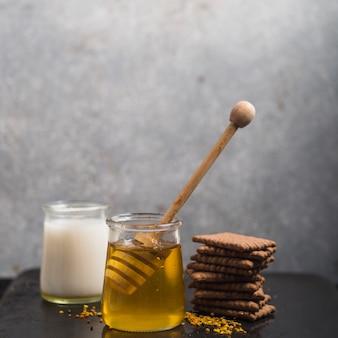 Pila de galletas caseras; leche y miel olla con cucharón de miel