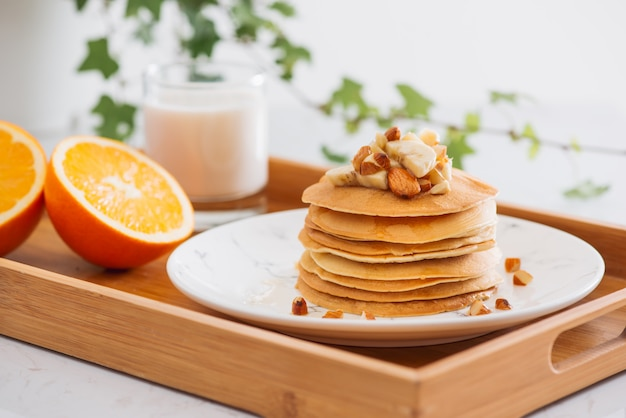 Pila de deliciosos panqueques con chocolate, miel, nueces y rodajas de plátano en la placa sobre fondo de piedra