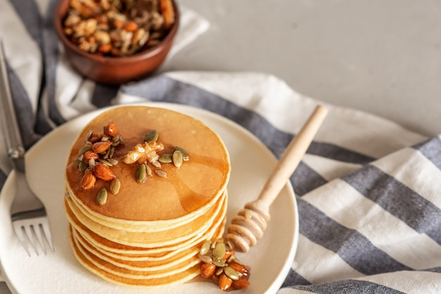 Pila de deliciosos panqueques con chocolate, miel, nueces y rodajas de plátano en plato y servilleta en madera