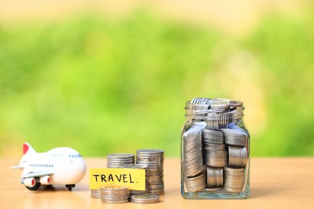 Pila de dinero de las monedas en la botella de cristal y el aeroplano en fondo verde natural