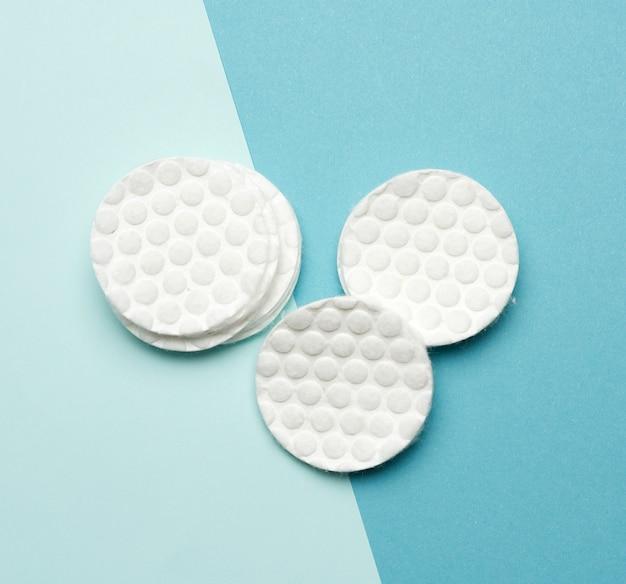 Pila de discos redondos de algodón blanco para procedimientos cosméticos sobre un fondo azul.