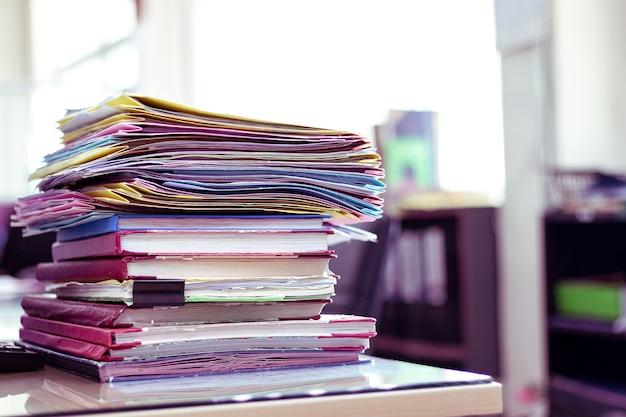 Pila de documentos colocados en un escritorio de negocios en una oficina de negocios.