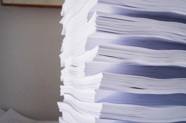 Pila de documentos y documentos de archivos de informes sobre el trabajo de sobrecarga en la oficina de escritorio
