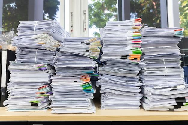 Pila de documentos sin terminar en el escritorio de oficina