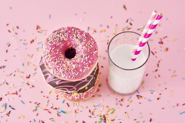 Pila de donas de colores decorados y un vaso de leche en rosa