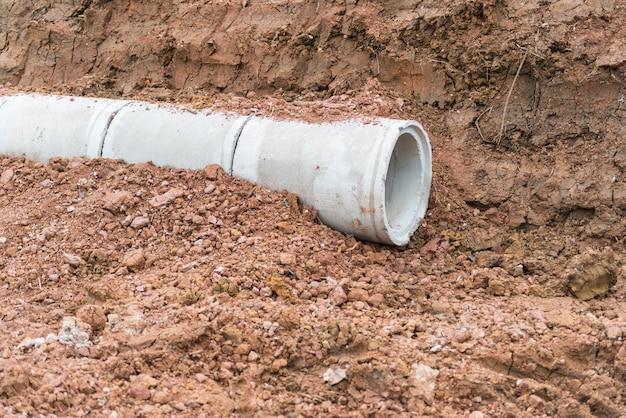 Pila de drenaje de concreto excavación de tuberías en un sitio de construcción. tubería de hormigón apilada aguas residuales
