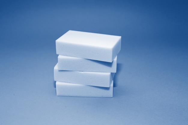 Pila de esponja doméstica de melamina con cuatro esponjas para limpiar sobre fondo azul en tonos de color azul clásico de moda del año 2020.