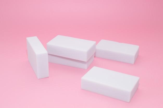 Pila de esponjas de melamina para el hogar con cuatro esponjas para limpiar sobre fondo rosa.