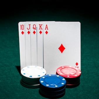 Pila de fichas de casino en frente de la tarjeta de juego de escalera real en la mesa de póquer