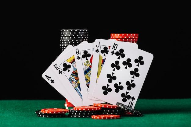 Pila de fichas de casino y naipe de escalera real en la mesa de póker verde