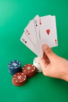 Pila de fichas y mano con cuatro ases, paño de póquer, una baraja de cartas, mano de póquer y fichas.