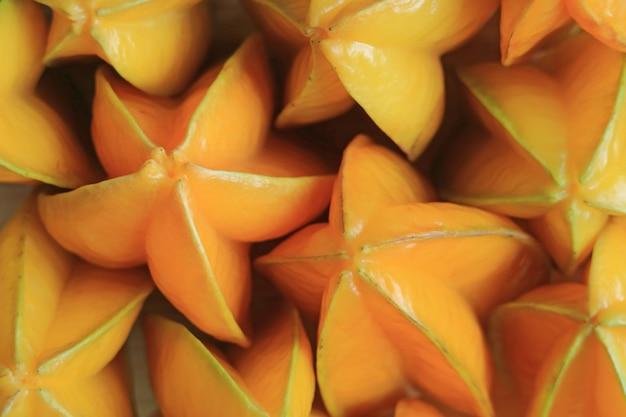 Pila de frutas de estrella frescas maduras amarillas anaranjadas vibrantes para el fondo