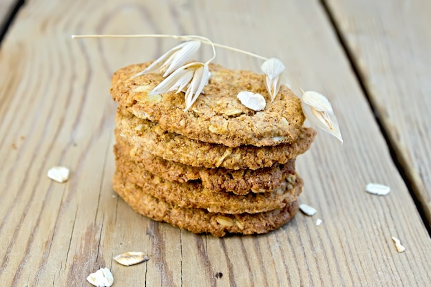Pila de galletas de avena con cereales y un tallo de avena en el fondo de tablas de madera
