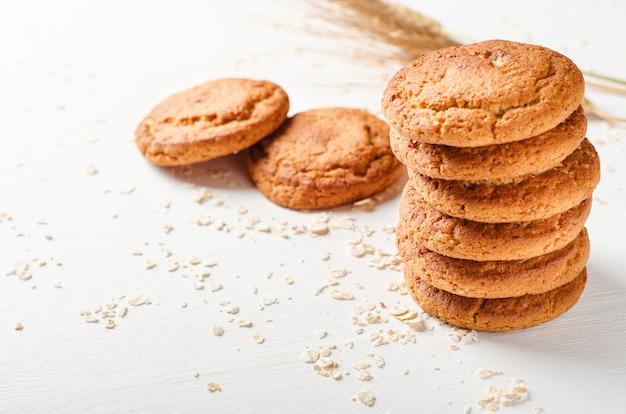 Una pila de galletas de avena con copos de avena en una mesa de madera blanca