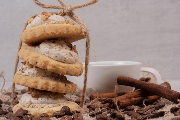 Pila de galletas de avena, taza y canela en el cuadro blanco.