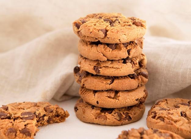 Pila de galletas con chispas de chocolate delante de tela