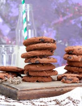 Pila de galletas de chispas de chocolate redondas sobre una tabla de madera marrón