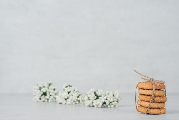 Pila de galletas con flor blanca sobre superficie blanca.