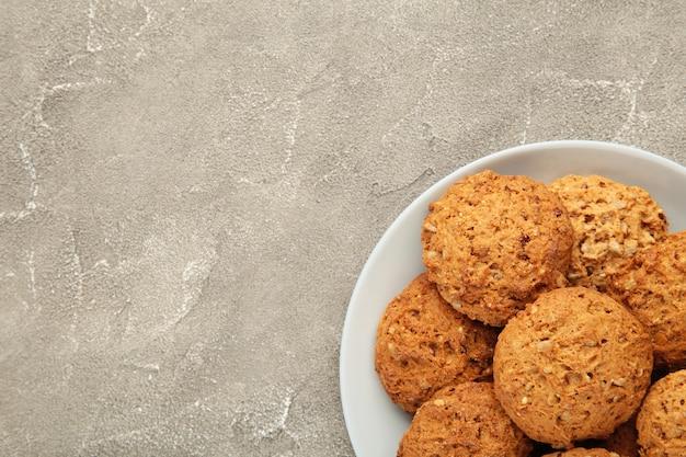 Pila de galletas en el plato sobre fondo gris.