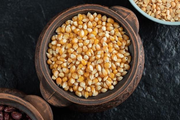 Pila de granos de maíz crudos en taza antigua.