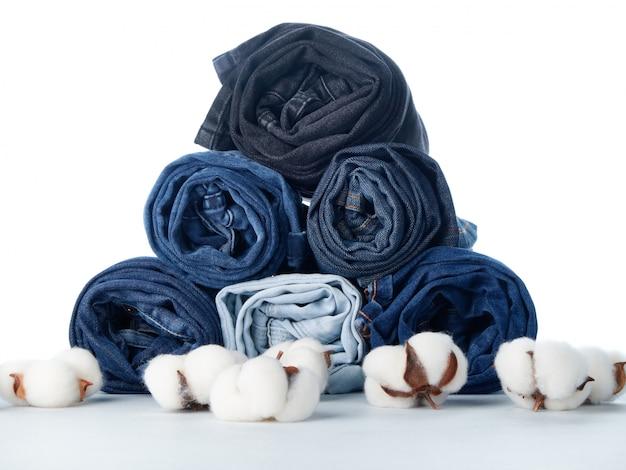 Pila de jeans enrollados y flores de algodón