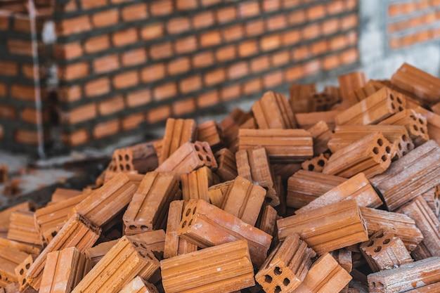 Pila de ladrillo que se prepara para mansonry sobre la foto borrosa de fondo de la pared de ladrillos,