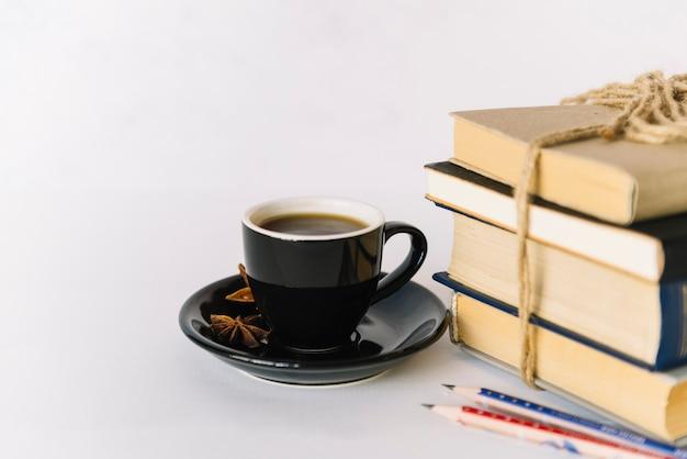 Pila de libros al lado de taza de café