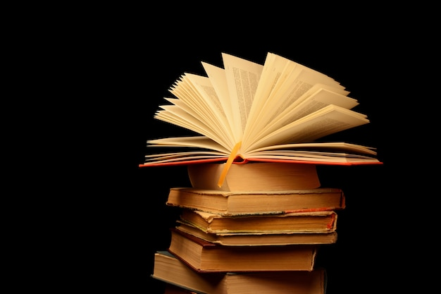 Pila de libros antiguos sobre un fondo negro