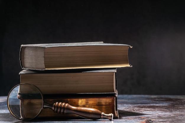 Una pila de libros antiguos sobre una mesa sobre un fondo oscuro y lupa.