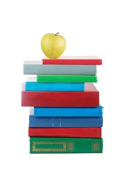 Pila de libros y apple aislado sobre superficie blanca