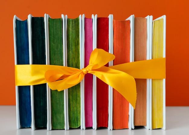 Pila de libros de arco iris con cinta amarilla