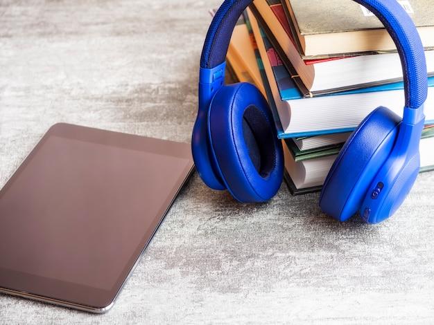 Pila de libros con auriculares en la mesa