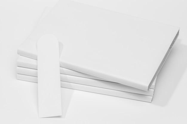 Pila de libros blancos y vista frontal de marcadores