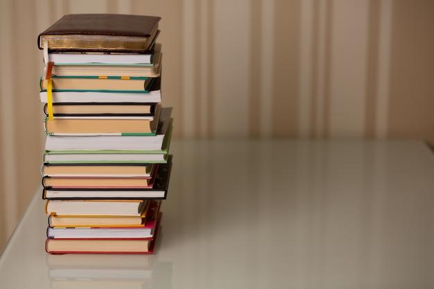 Pila de libros en casa. fondo de rayas beige. copia espacio