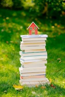 Pila de libros y una casita sobre la hierba verde en otoño