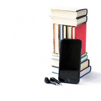 Pila de libros de colores, auriculares y teléfono móvil.