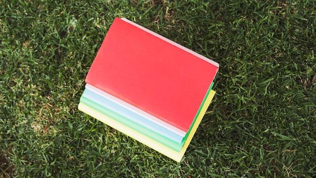 Pila de libros coloridos sobre hierba