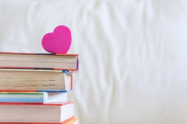 Pila de libros y corazón rosa en la cama blanca