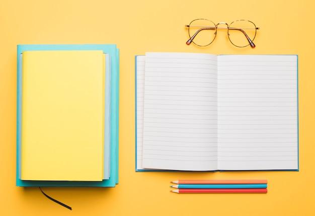 Pila de libros y cuaderno abierto en blanco con lápices arreglados