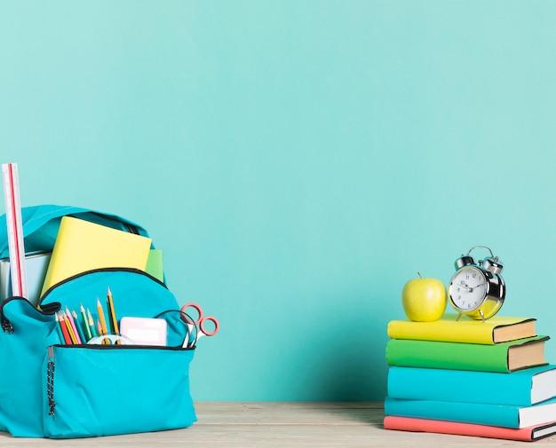Pila de libros despertador y mochila escolar con suministros.