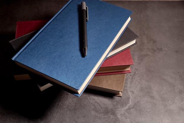 Pila de libros de diferentes colores junto a un bolígrafo.